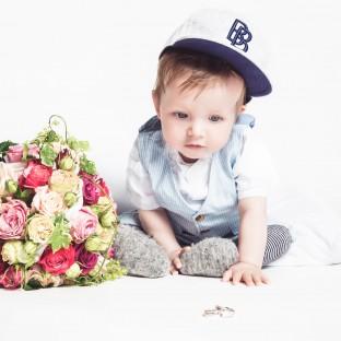 Baby mit Cap, Brautstrauss und Eheringen