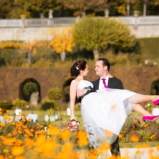 Mann trägt Braut im Rosengarten