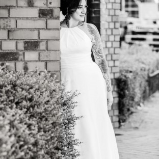 Braut steht an Mauer im Garten