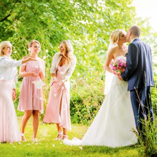 Hochzeitspaar mit Brautjungfern im Wald