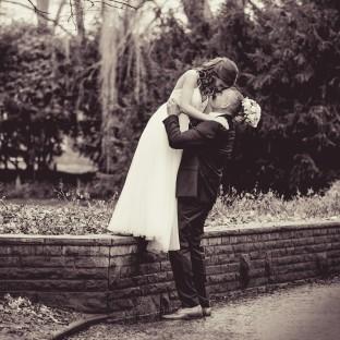 Mann trägt Ehefrau und küsst sie