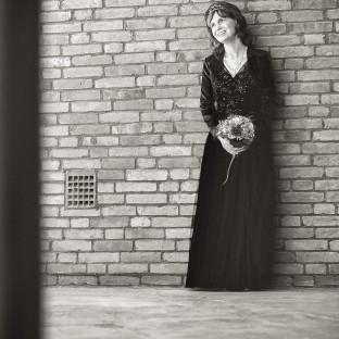Braut an Steinwand vor der Kirche