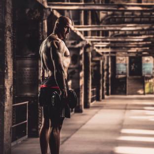 Foto von Mann mit Hanteln in Fabrik
