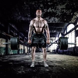 Muskulöser Mann Aktfoto mit Langhantel