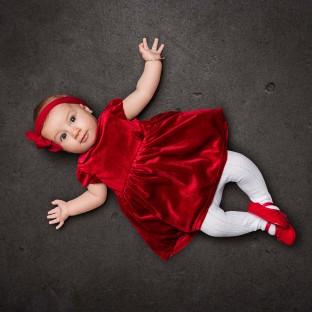 Baby im roten Kleid im Fotostudio