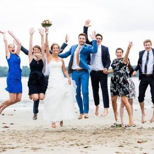 Hochzeitsgesellschaft am Strand springend