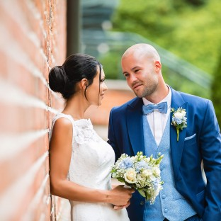 Schönes Brautpaar an Mauer gelehnt