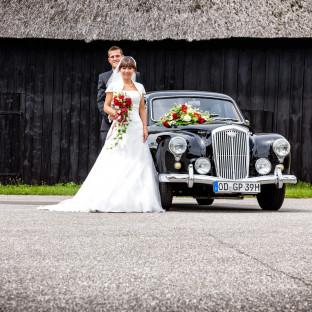 Brautpaar mit Oldtimer an schwarzer Scheune