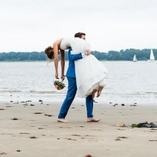 Mann trägt Braut am Strand