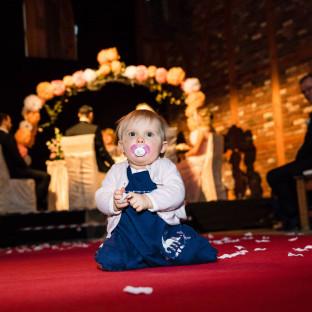 Kind hinter Paar bei Hochzeit