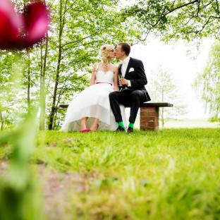 Brautpaar hinter Mohnblume auf Bank