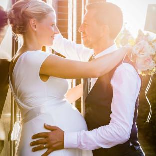 Romantische Gegenlichtaufnahme von Brautpaar mit schwangerer Braut
