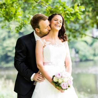 Mann küsst Braut auf Hals