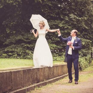 Braut mit Schirm auf Mauer