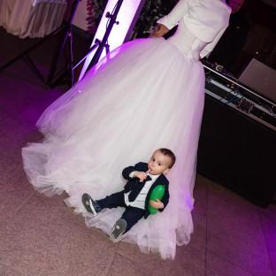 Kind sitzt auf Brautschleier