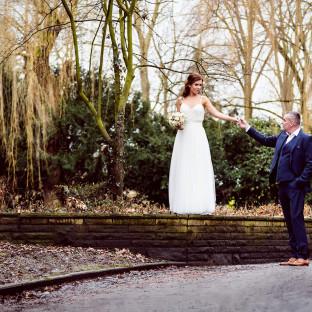 Braut auf Mauer mit Ehemann an der Hand