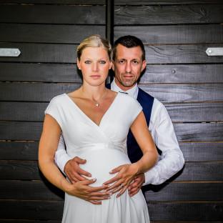Schwangere Braut mit Ehemann bei Hochzeit