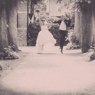 Brautpaar am Springen in einer Allee