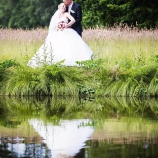 Brautpaar spiegelt sich im Wasser in Glinde