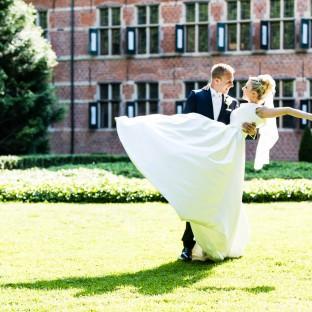 Mann trägt Braut vorm Schloss