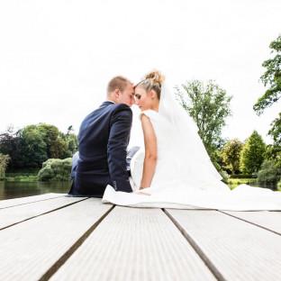 Hochzeitspaar sitzt auf Steg