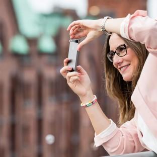 Frau beim Fotografieren mit Handy in der Speicherstadt